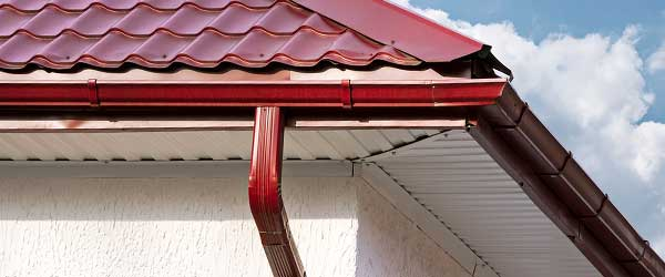 Red seamless gutter system installation with matching red roof