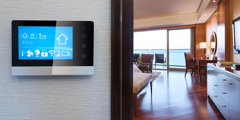 Smart thermostat attached to a wall, displaying it's home screen