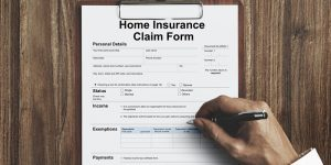 while male beginning to fill out a home insurance claim form