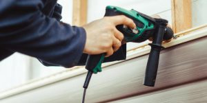 A hard-working renovator installing vinyl siding with a power drill