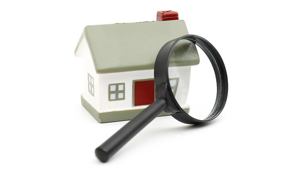 Magnifying glass aimed on miniature house for home siding inspection