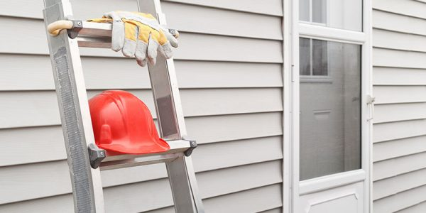 Orange hardhat and gloves placed on a ladder resting on grey vinyl siding